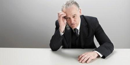 man in bussiness suit, at desk, looking depressed