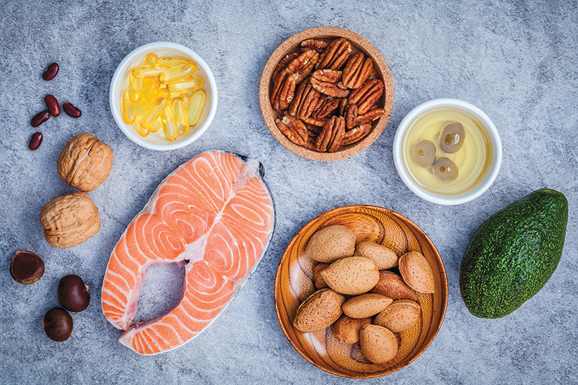 Selection food sources of omega 3 and unsaturated fats. Super food high omega 3 and unsaturated fats for healthy food. Almond pecan hazelnutswalnuts olive oil fish oil salmon and avocado on stone background .